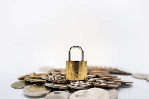 Gros plan de serrure de clé principale or sur le tas de pièces de monnaie avec espace de copie. Photo Premium