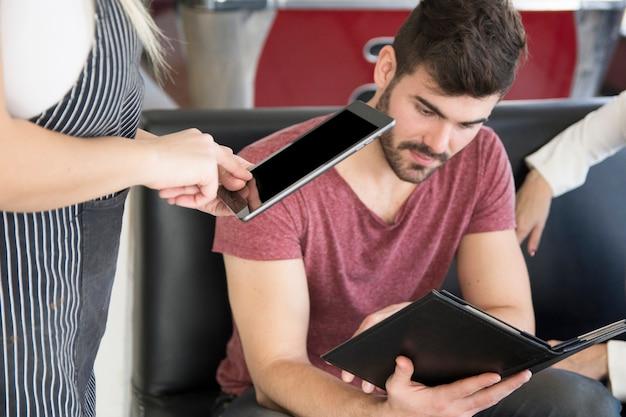 Gros plan, serveuse, prendre, commande client, sur, tablette numérique Photo gratuit