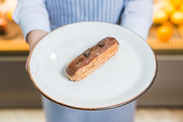 Gros plan, de, serveuse, tenue, tranche gâteau, sur, plaque blanche Photo gratuit