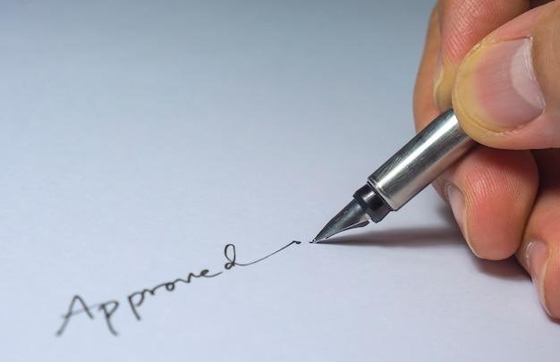 Gros plan de la signature approuvée avec les doigts et le stylo, ampoule du côté gauche Photo gratuit