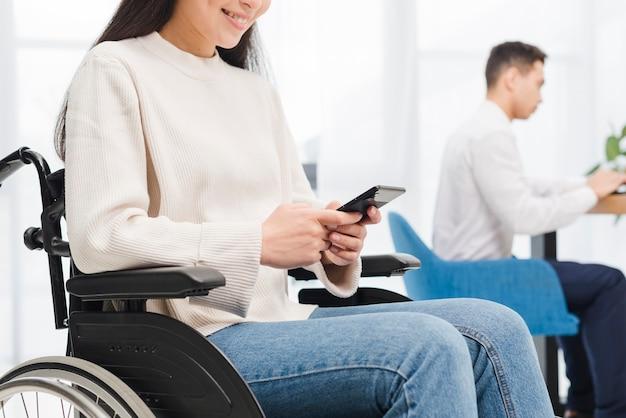 Gros plan, sourire, handicapé, jeune femme, s'asseoir fauteuil roulant, utilisation, téléphone portable, devant, son, collègue Photo gratuit