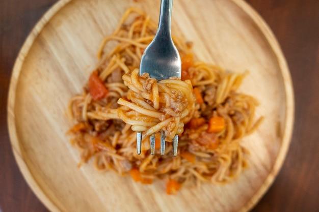 Gros plan de spaghetti sur un plat en bois Photo Premium