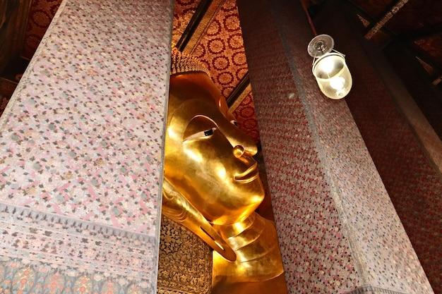Gros Plan De La Statue Dorée De Bouddha Dans Le Complexe Du Temple Bouddhiste Wat Pho, Thaïlande Photo gratuit