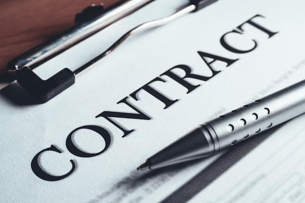 Gros plan d'un stylo en argent placé sur les documents de l'accord sur les contrats. signature du contrat légal. Photo Premium