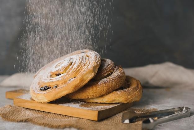 Gros plan, sucre, saupoudrer, à, cannelle cuit, brioches, sur, planche découper Photo gratuit