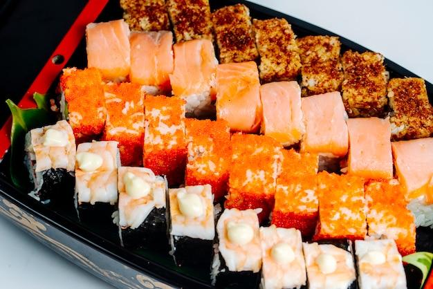 Gros plan de sushi serti de saumon, crevettes, tobiko rouge et rouleaux chauds Photo gratuit