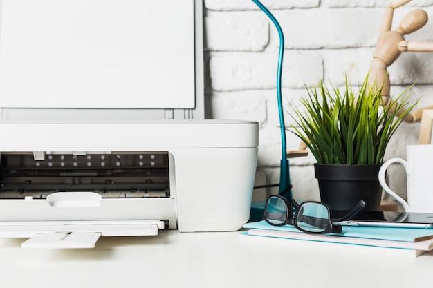 Gros plan d'une table de travail à la maison avec imprimante et fournitures Photo Premium