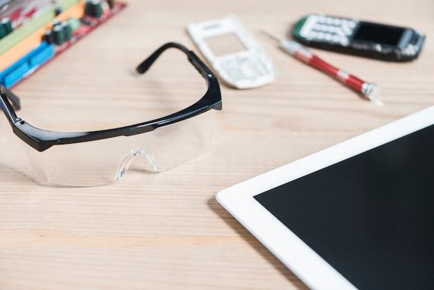 Gros plan, de, tablette numérique; lunettes de sécurité et téléphone portable cassé sur fond en bois Photo gratuit