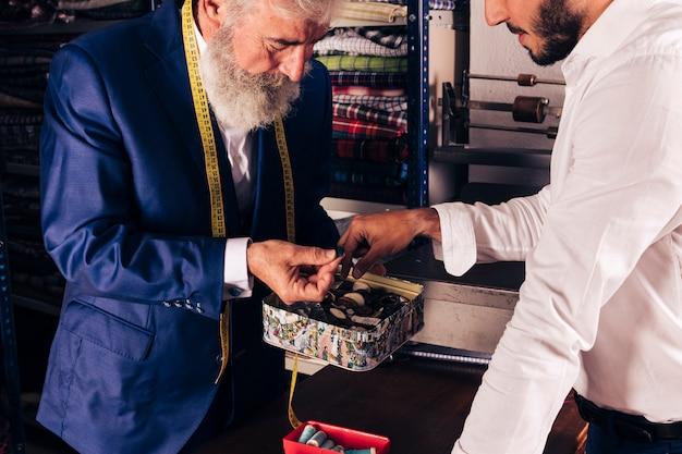 Gros plan d'un tailleur senior avec un ruban à mesurer autour du cou montrant le bouton à son client Photo gratuit