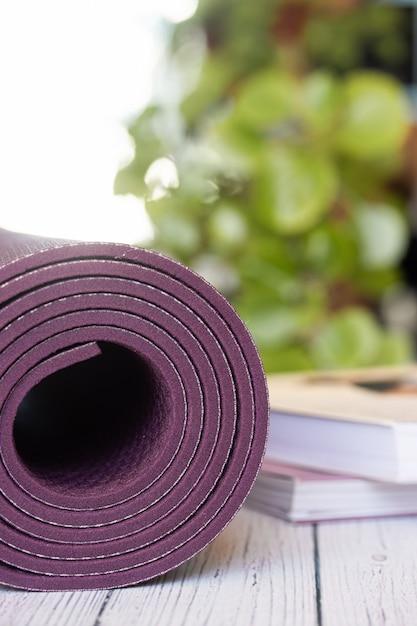 Gros Plan D'un Tapis De Yoga Violet Avec Des Livres Sur Un Plancher En Bois Blanc. Photo Premium