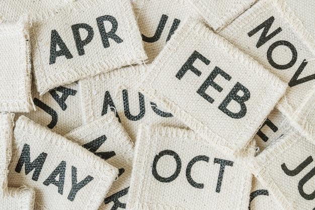 Gros plan tas de calendrier de petit tissu en arrière-plan texturé de nombreux mois Photo Premium