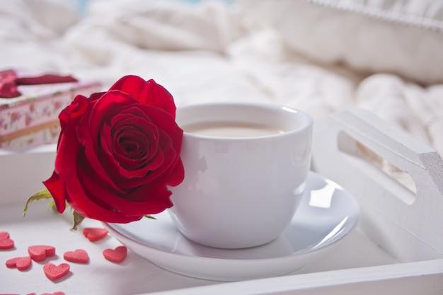 Gros plan, de, tasse thé, à, rose rouge, et, petit bonbon, coeurs, sur, les, table Photo Premium