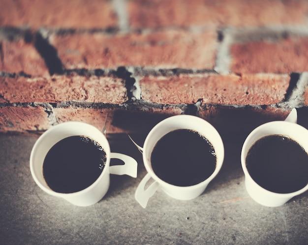Gros plan de tasses à café avec fond de mur de brique Photo gratuit