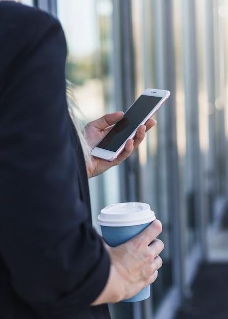 Gros plan, de, tenue femme, jetable, tasse café, à, téléphone portable Photo gratuit