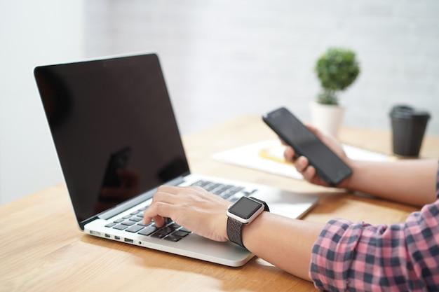Gros plan, de, tenue femme, smartphone, à, travailler, sur, ordinateur portable Photo Premium