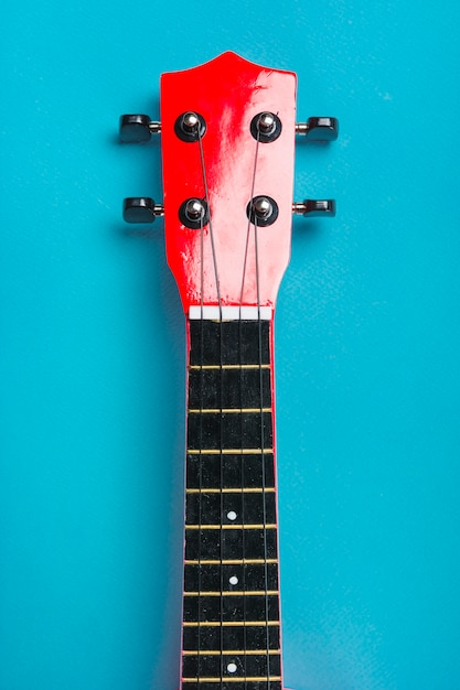 Gros plan d'une tête de guitare classique acoustique sur fond bleu Photo gratuit