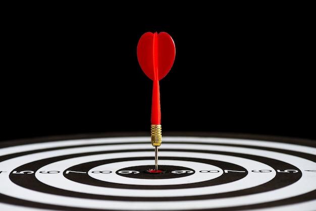 Gros plan tir fléchettes de fléchettes rouges dans le centre de la cible sur fond noir. Photo Premium