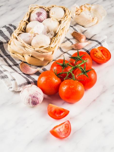 Gros plan de tomates fraîches et juteuses; oignons; gousses d'ail et chiffon sur fond de marbre Photo gratuit