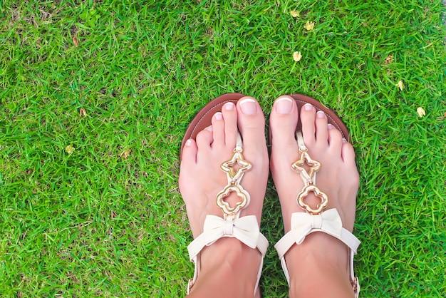 Gros plan de tongs lumineux et les jambes sur l'herbe verte Photo Premium