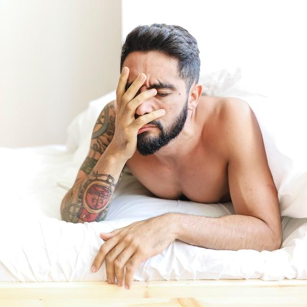 Gros plan, triste, jeune homme, coucher lit Photo gratuit