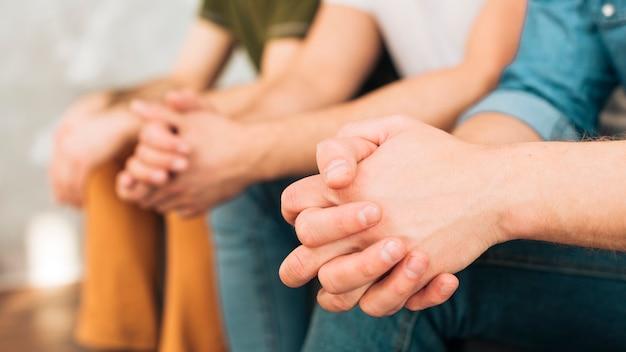 Gros plan, trois, amis hommes, s'asseoir ensemble, à, leurs mains jointes Photo gratuit