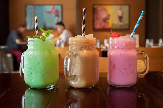 Gros Plan De Trois Savoureux Savoureux Thé Au Lait Thaïlandais Sur Une Table En Bois Dans Un Café Photo gratuit