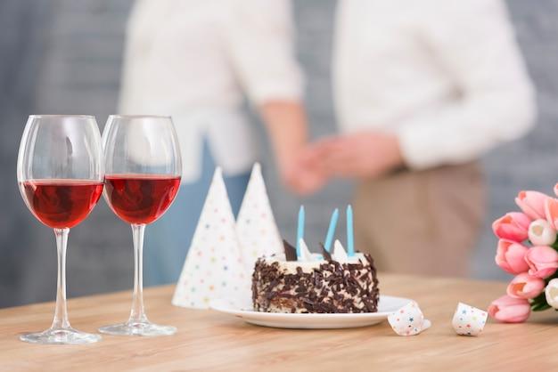 Gros plan, verre à vin; gâteau délicieux; corne de fête et fleurs de tulipes sur le bureau en bois Photo gratuit
