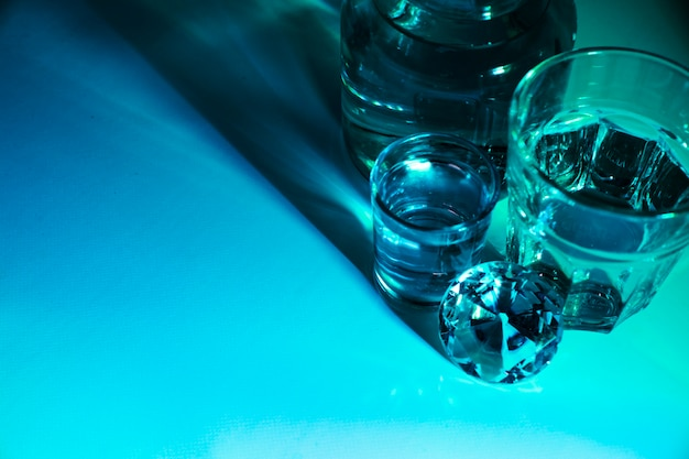 Gros plan, de, verres eau, et, bouteille, à, diamant, sur, bleu, clair, fond Photo gratuit