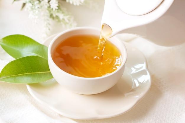 Gros plan versant le thé noir chaud dans une tasse de thé blanc Photo Premium