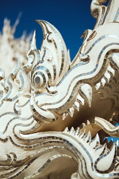 Gros Plan Vertical Tiré D'une Statue De Dragon Dans Le Temple Blanc De Chiang Rai, Thaïlande Photo gratuit