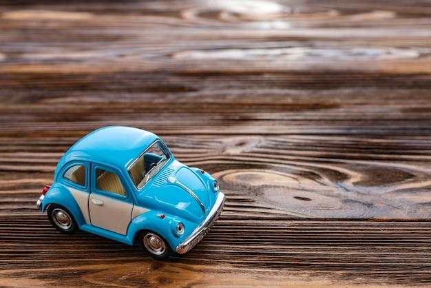 Gros plan d'une voiture de jouet sur un fond en bois. Photo Premium