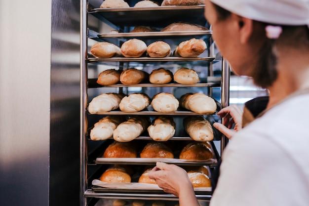 Gros Plan, Vue, Femme, Tenue, Tenue, étagère, Pains, Dans, Une, Boulangerie Photo Premium