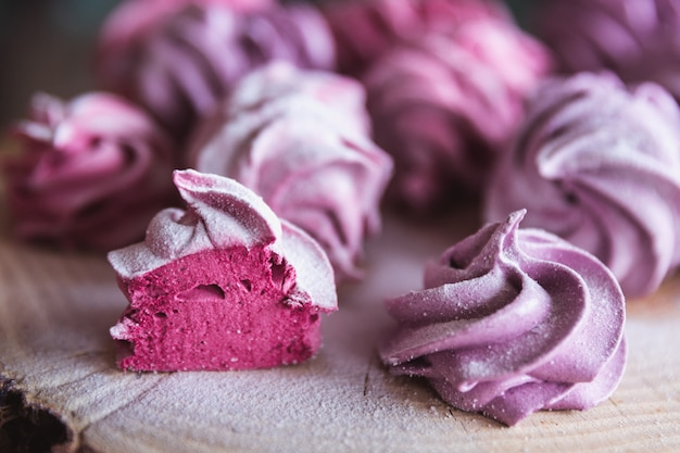 Gros plan de zephyr ou de guimauve rose coupé maison en sucre en poudre sur bois Photo Premium