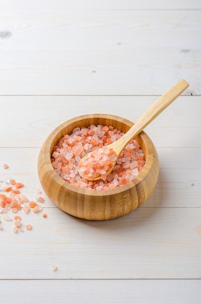 Gros sel rose de l'himalaya dans un bol en bois avec une cuillère sur un fond en bois blanc. Photo Premium