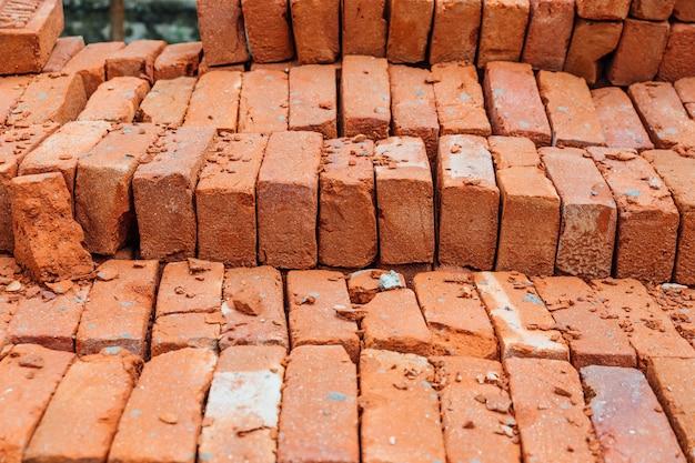 Gros tas de texture de brique rouge avec de la mousse sur certaines briques. Photo Premium