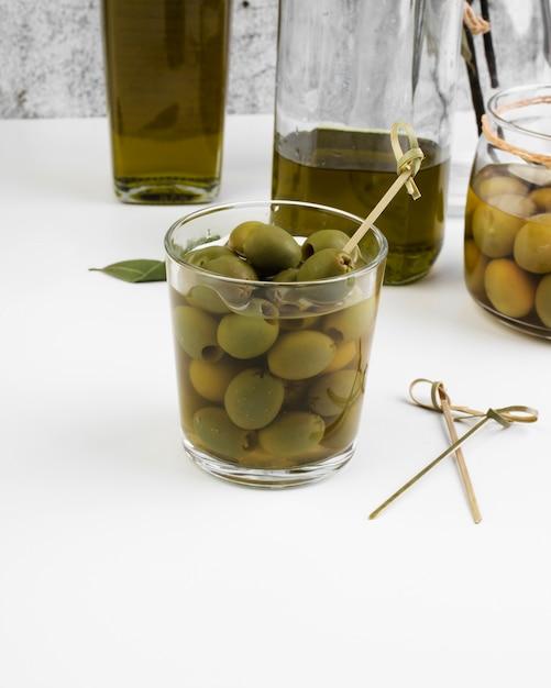 Gros verre rempli d'olives fraîches Photo gratuit