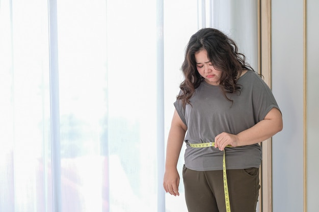 La Grosse Femme Asiatique Est Triste à Cause De L'augmentation De La Taille Après Avoir Vérifié Avec Un Ruban à Mesurer. Photo Premium