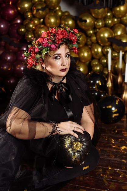 Une Grosse Sorcière Adulte En Vêtements Noirs Et Avec Des Larmes D'étincelles Tient Une Citrouille Noire Photo Premium