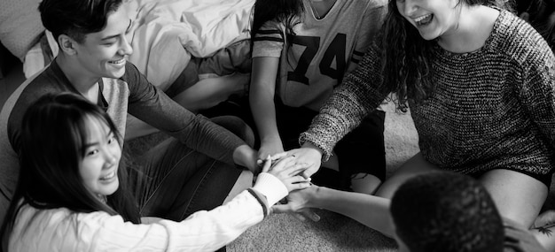 Groupe d'adolescents dans une chambre à coucher mettant leurs mains ensemble concept de communauté et de travail Photo gratuit