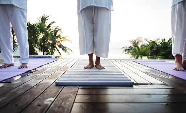Groupe d'aînés pratiquant le yoga au bord de la piscine Photo Premium