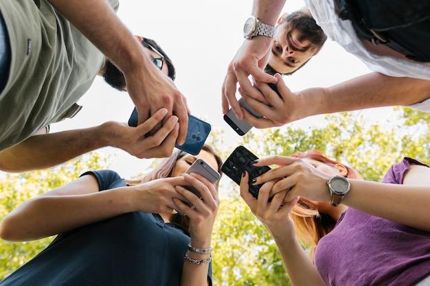 Groupe D'amis Adultes Debout Et Textos Ensemble Photo Premium