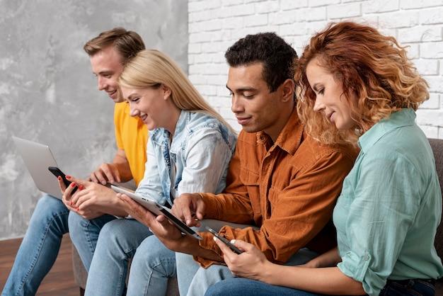 Groupe d'amis avec des appareils électroniques Photo gratuit