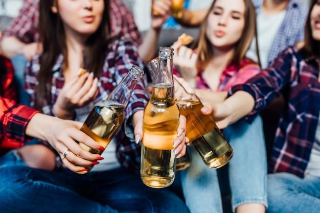 Groupe d'amis applaudir avec des bières à la maison interiour, se fermer. Photo Premium