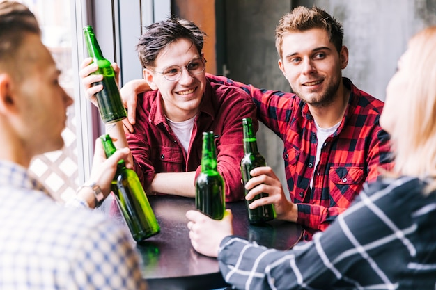 Groupe d'amis assis autour de la table en dégustant une boisson au restaurant du pub Photo gratuit