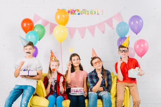 Groupe d'amis assis sur un canapé avec un gâteau d'anniversaire; ballons et cadeaux Photo gratuit