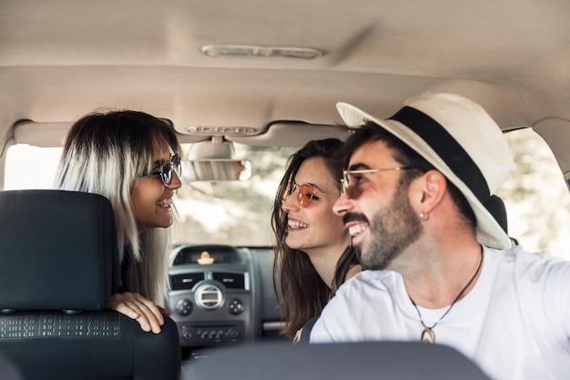 Groupe d'amis assis à l'intérieur de la voiture s'amuser Photo gratuit