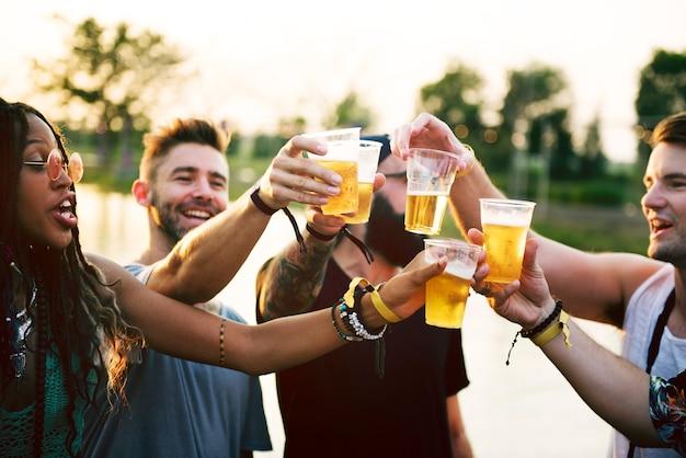 Groupe d'amis buvant de la bière profitant d'un festival de musique ensemble Photo Premium