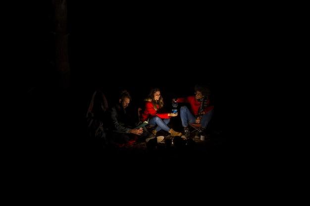Groupe d'amis campant la nuit Photo gratuit