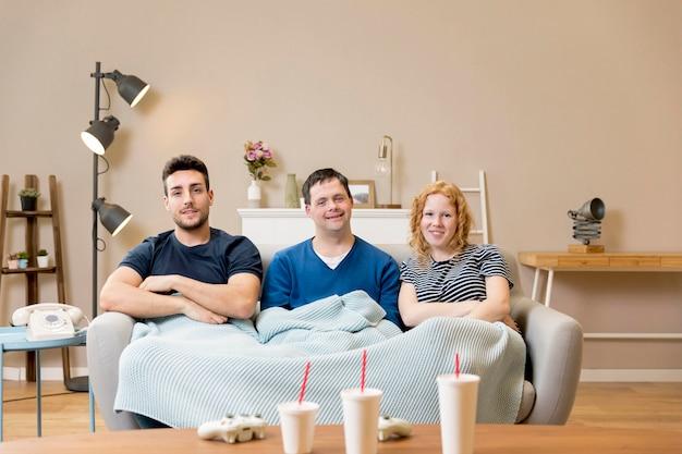 Groupe D'amis Sur Le Canapé Avec Des Sodas Et Une Couverture Photo gratuit