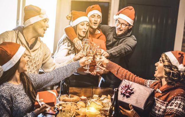 Groupe D'amis Avec Des Chapeaux De Père Noël échangeant Des Cadeaux De Noël Avec Un Toast Au Champagne Lors D'un Dîner à La Maison Photo Premium
